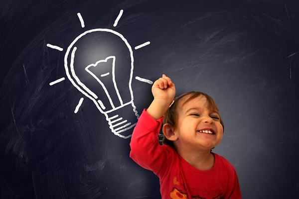 Little cute girl having a good idea on the blackboard - Learning and discovery concept with lightbulb