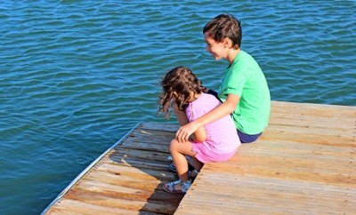 Companionship - older brother embracing little sister on the pier